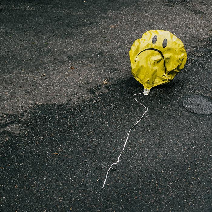 Newsbild: trauriger Smiley Luftballon mit wenig Luft